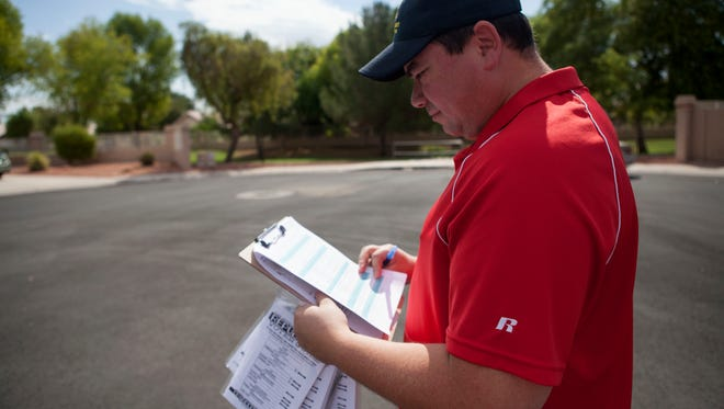 Chandler City Council candidate Rene Lopez walks door-to-door canvassing a neighborhood for votes.