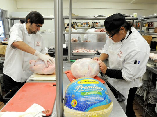 Rancho Cielo Drummond Culinary Academy students Daniel Morales and Bryanne Velarde work on breaking down turkeys for the Castroville Community Feast on Thursday.