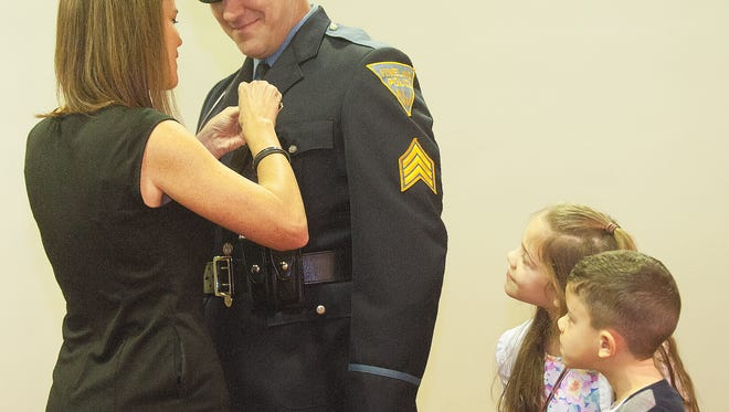 Mary Anne Wolf places the lieutenant badge on her husband Lt. Leonard Wolf , next to his kids Claire and Connor, during a swearing ceremony by the Vineland Police Department at the Vineland City Hall.
