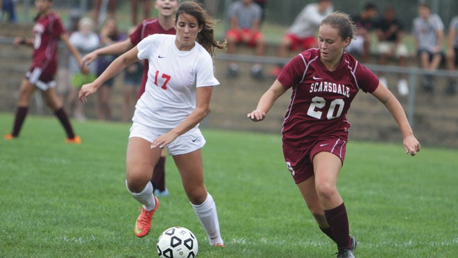 Scarsdale's Sam Mancini (maroon) defends against North Rockland's Brianna Williams during a game at North Rockland High School on Saturday, September 12th, 2015. North Rockland won 2-0.