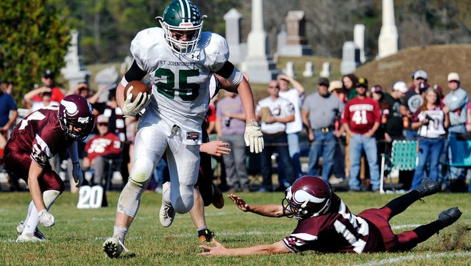 St. Johnsbury's Mat Roy breaks through the Lyndon defense during the first half of the Hilltoppers' 61-14 win in the 113th playing of The Game at Robert K. Lewis Field on Saturday, Oct. 21, 2017.