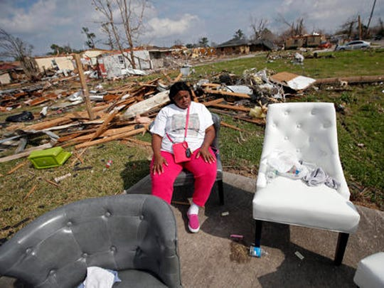 Sheila Jefferson sits outside a relatives home as friends remove salvageable possessions, in the aftermath of Tuesday's tornado that tore through the New Orleans East section of New Orleans, Wednesday, Feb. 8, 2017.  Officials say tornadoes that struck in southeastern Louisiana destroyed homes and businesses, flipped vehicles and left thousands without power.