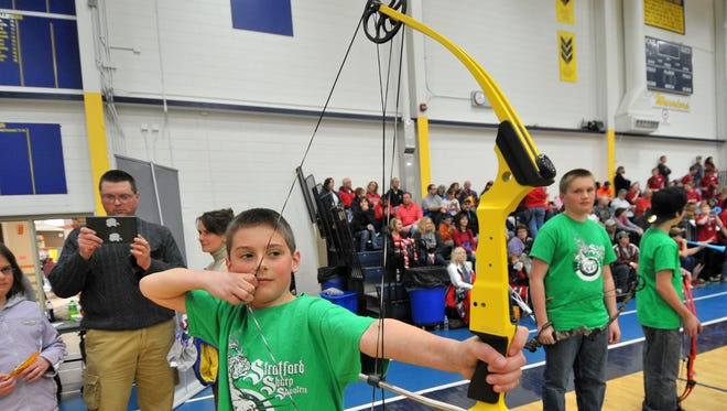 Addison Schafer, 10, of Stratford, flex his bow while on a short break during the 2014 National Archery in Schools state tournament at Wausau West High School fieldhouse.
