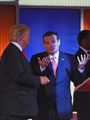 Donald Trump speaks with Ted Cruz during a break at