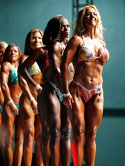 Michelle Reynolds-Madden 40, of Fort Thomas, front poses for judges during the fifth annual Kentucky Derby Festival Championships of bodybuilding at the The Kentucky International Convention Center in Louisville Saturday April 30, 2016. The competition was a first for the Reynolds-Madden.
