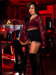Deanna Roisin wears a burgundy lace bell-sleeve crop top from Forever 21; black lace bralette from Victoria's Secret; high-waisted lace-up shorts from Crash Bang Boom; and velvet thigh-high boots from Marshalls.