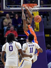 Florida center Kevarrius Hayes (13) dunks in front of LSU forwards Naz Reid (0) and Kavell Bigby-Williams (11) during the first half of an NCAA college basketball game Wednesday, Feb. 20, 2019, in Baton Rouge, La. (AP Photo/Bill Feig)