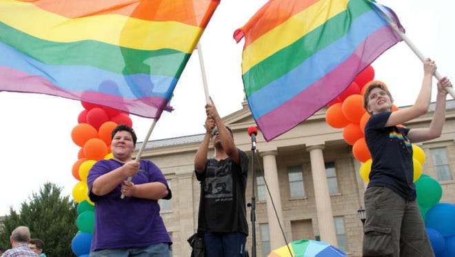 Iowa City Pride chair Jewell Amos, from left, CoCo Moreno and McKinley BarbouRoske wave pride flags during a rally on the Pentacrest celebrating the Supreme Court's ruling on the Defense of Marriage Act on Wednesday, June 26, 2013.