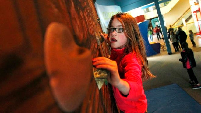 Fiona Clifford, 10, of Trumansburg, in town visiting family in Fairport and Victor, maneuvers around on the rock climbing wall at the RMSC's Holiday Science and Technology Days in Rochester.