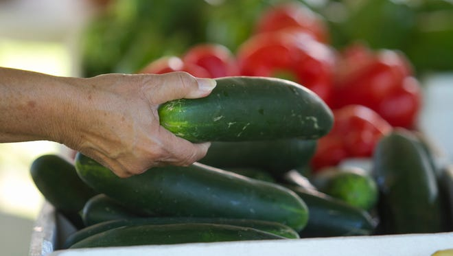 A customer shops for cucumbers at the Brittain Farms booth at the Green Market at the Alliance for the Arts on Saturday.