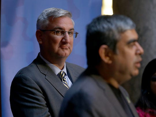 Governor Eric Holcomb,left, listens to the announcement Tuesday. May 2, 2017, at the Indiana Statehouse  by Infosys CEO Dr. Vishal Sikka his company to bring 2000, high-skilled high tech to central Indiana by the end of 2021. Indiana