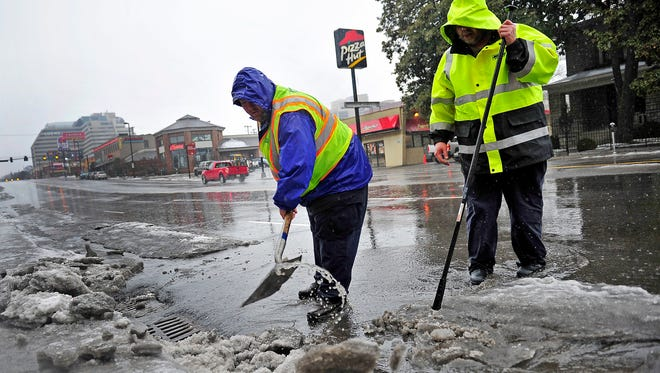 The Metro Water Services crews work to clear water drains on West End in Nashville, Tenn., Saturday, Feb. 21, 2015.