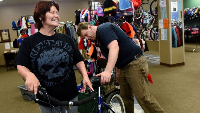 Evee Bordeaux is all smiles after buying herself a new bike while while the Center for Hope's bike ministry coordinator John Blok adjust the seat at the Center for Hope in downtown Sioux Falls on Tuesday, May 24, 2016.