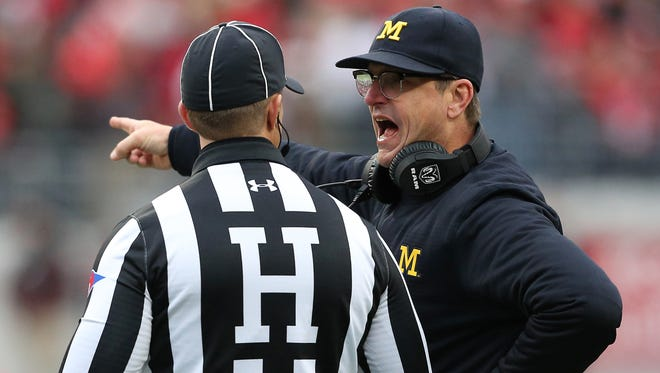 Michigan coach Jim Harbaugh's post-game comments about officiating Saturday got him a reprimand and the university a $10,000 fine on Monday.
