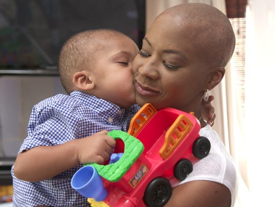Dr. Lori Wilson gets a kiss from her son after shaving