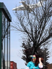 Diane Romano of South Hackensack waits for a bus Tuesday as a plane flies over Route 46 on its way to Teterboro Airport.