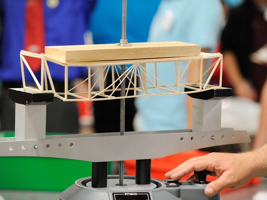 View of a wooden structure, built by students, being tested for its structural capacity at the Technology Student Association competition at the Delaware State Fairgrounds.