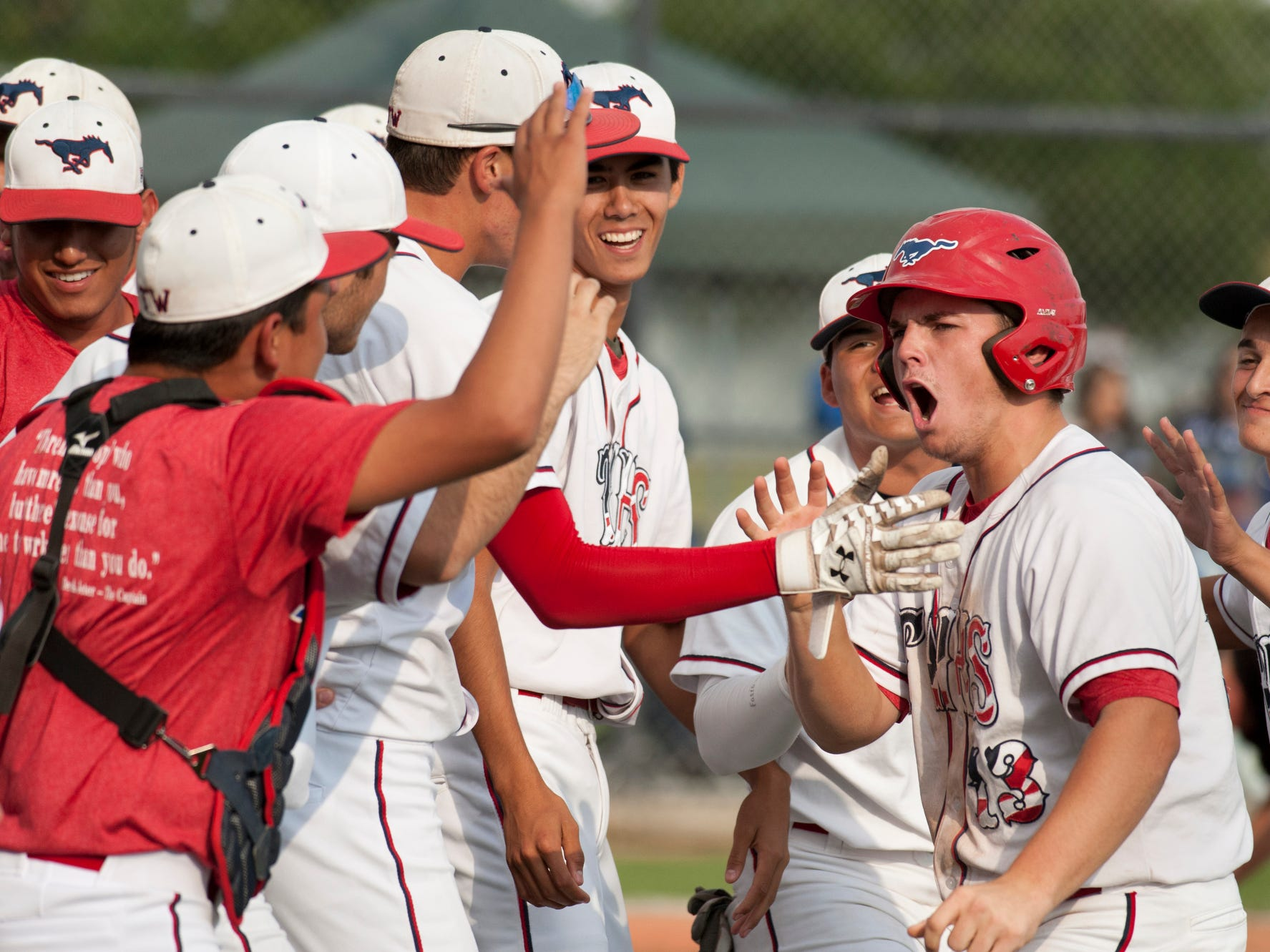 Tulare Western's Drew Muller and teammates celebrate a run generated by Blake Costa that put the Mustangs up 4-2 during Friday's Central Section playoff game.