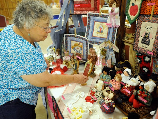 Glenda Seawel of Harrison checks out handmade dolls during Craftfest at the Baxter County Fairgrounds