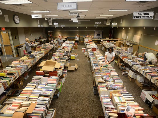 Volunteers set up books at the downtown library, Wednesday in preparation for a book sale starting Thursday.