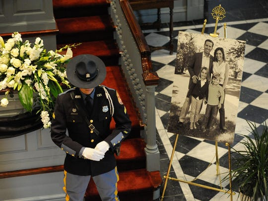 "A police officer stands next to a photo of Joseph R. ""Beau"" Biden III family at Legislative Mall in Dover."