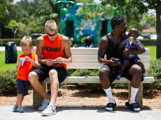 Travis Hewitt and his son Desmond, 3, and Mac gue and his son Malik, 2, from left to right, cool off with some snow cones during a Juneteenth & Father's Day event in Fort Myers on Saturday. The Housing Authority of the City of Fort Myers put on its fifth annual Father's Day Celebration with youth and adult basketball competitions, flag football, music, stage performances and kids' activities.