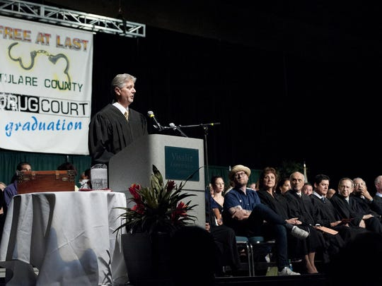 Judge Gary Johnson, left, addresses family and friends of the more than 200 graduates from the Tulare County Adult Drug Court on Monday, June 22, 2015.