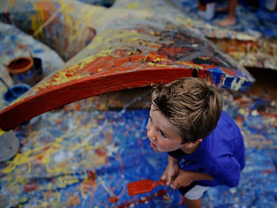 Wilson Ireland, 4, Waukee, steps out from under the goldfinch sculpture created by artist Bounnak Thammavong as part of his, Birds of a Feather project during the Des Moines Art Festival in Western Gateway Park on Friday, June 26, 2015.