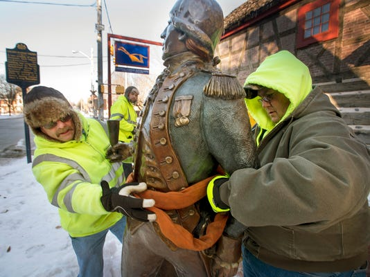 York city workers Ron Schrum, left, and Dave Rudolph fit statue for the ride up into the truck. The Marquis de Lafayette statue is removed from in front of the Golden Plough Tavern for a repair to the base at Kottcamp Sheet Metal Tuesday February 24, 2015  Paul Kuehnel - Daily Record/Sunday News