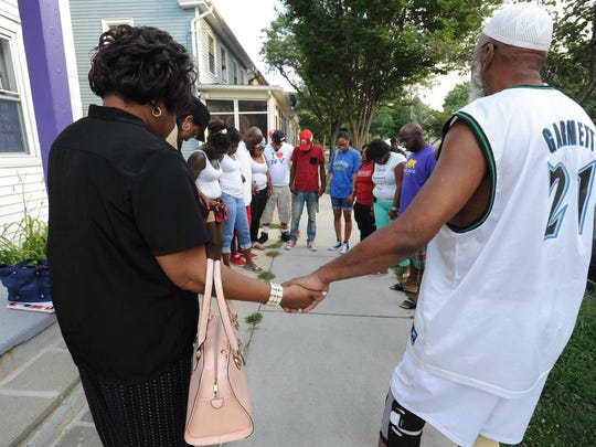 People pray Saturday before a meeting, at the Faith House Outreach Center in Dover, called to discuss the shooting of Terrance Fletcher in the thigh by a police officer after a foot chase through downtown Friday.