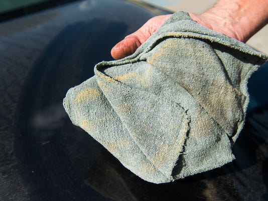 Hanover resident Paul McGee wiped the hood of his car to show how much pollen was on the hood of his car.