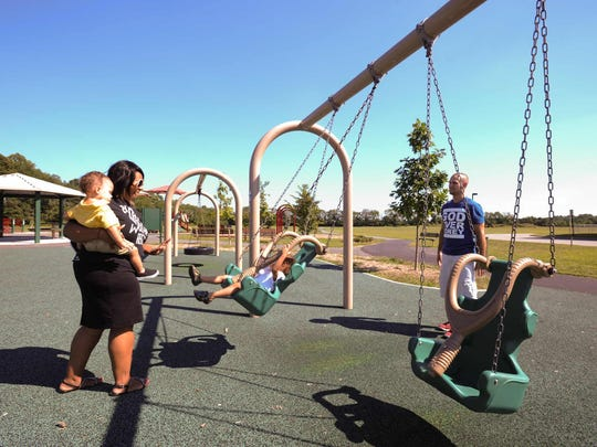 Christopher and Ebonee Johnson of Lincoln play with their sons Harrison (1) and Giovanni (3) at the Milford Can-Do playground.