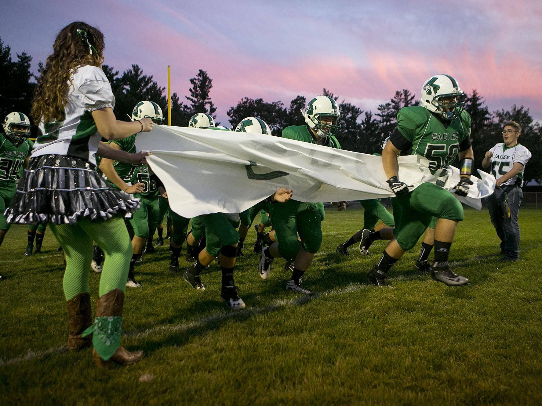 Almond-Bancroft's Cole Warzynski (58) leads the team onto the field for the Central Wisconsin Conference football game against Wild Rose in Almond, Friday, Sept. 25, 2015.