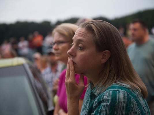 A woman in the audience listens to the meeting proceedings on Aug. 6, 2015 after the meeting was moved outside to the township building's garage.