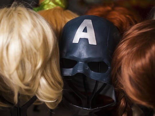 A Captain America mask sits on a stand surrounded by wigs for female characters. Though Graef has approximately 50 helpers, she has more difficulty finding men to than women.