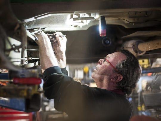 Myron Oatman replaces a truck's fuel pump in Ulmer's