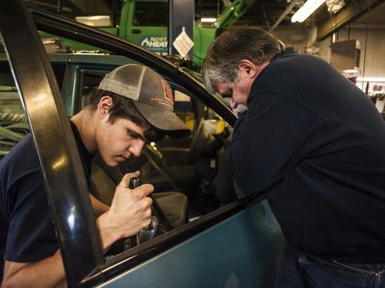 Josh Oatman, left, and Greg Ulmer, right, work on van