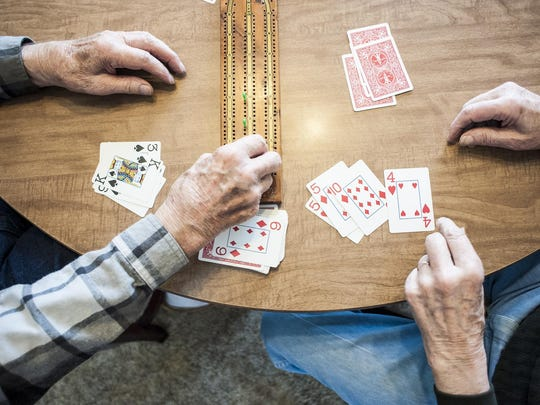 Jim Geiger, left, and Ted Garnett, right, play cribbage in Geiger's Conrad home. Only at a school Veterans Day event this year did Garnett learn Geiger was a World War II veteran, too.