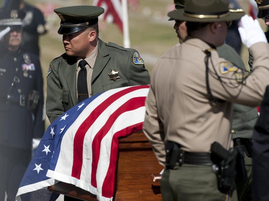 Deputy Keith Jung, left, and other casket bearers escort the body of Deputy Scott Ballantyne at the Visalia Cemetery on Monday. Ballantyne and pilot James Chavez were killed while on patrol Feb. 10.