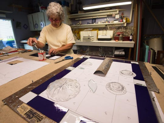 Gwen Schroll, who is a stained glass artist, works on a piece in her studio in Millsboro that will include several glass plates.