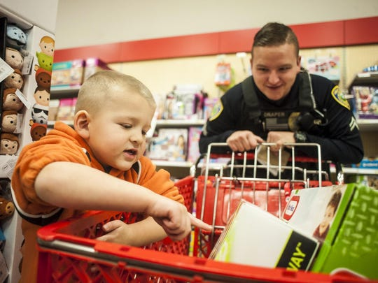 Cory Borror reviews his toy haul with Mike Draper during Shop with a Cop at Target on Tuesday.