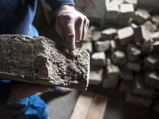 Mike Gittins points out details in a chipped adobe brick from the Officers Quarters of Fort Shaw in November during a reconstruction project. The building is one of the most important in Montana from the Indian Wars era.