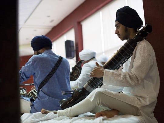 Jeevin Singh Neelam plays the dilruba during the Vaisakhi celebration.