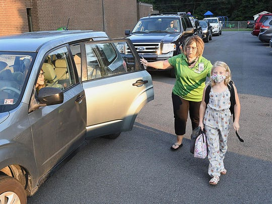 Hollywood Elementary School Principal Tamber Hodges, left, directs Aubree Gill to the school's entrance in Mabscott, W.Va., for the first day of school Tuesday morning.