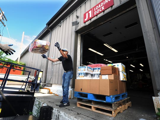 Guillermo Viscarra, a volunteer from the Franklin Food Pantry, throws boxes of food to Andy Keesan, not pictured, at the United Way of Tri Country food warehouse in Framingham, Massachusetts, last year.