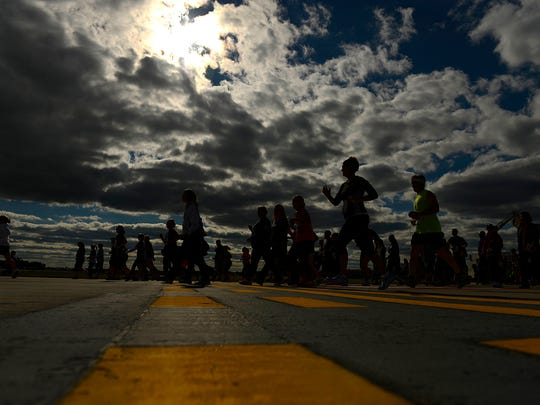 Runners are silhouetted against a cloudy sky as they race along the runway during the Prevea 5K GRB Run/Walk at Austin Straubel International Airport in Ashwaubenon on Saturday.