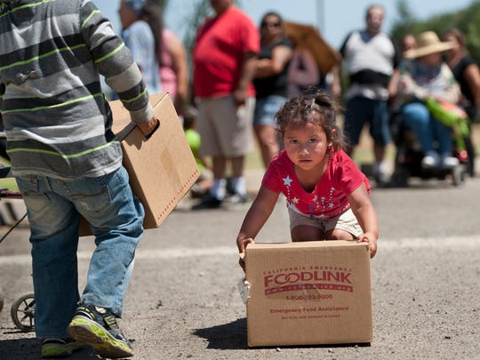 Juan Corona, 4, left, and his sister Heather Corona, 2, pick up boxes   at Bethel Spanish Assembly Church in Farmersville on   June 13.