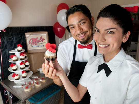 Mel Vidana and Nate Guevara, owners of Mel's Famous Bake Shop hold a chocolate with vanilla butter cream cupcake on Monday, Feb. 9, 2015.