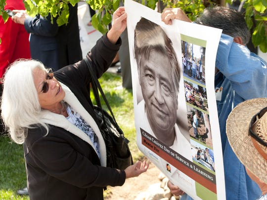 Patricia Guillen of Bellflower looks at a poster of Cesar Chavez during the U.S. Navy ceremony recognizing Chavez with graveside honors in the Memorial Garden of the Cesar E. Chavez National Monument in Keene on Thursday. Chavez served in the Navy from 1946 to 1948. Thursday was the 22nd anniversary of Chavez' death.