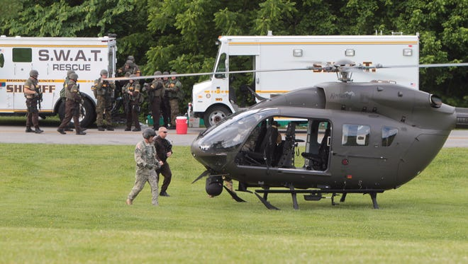 Crew members of a Kentucky National Guard helicopter move to board their aircraft as Boone Co. Sheriff SWAT members board an armored vehicle to enter Big Bone Lick State Park to search for David Lee Rickerson.